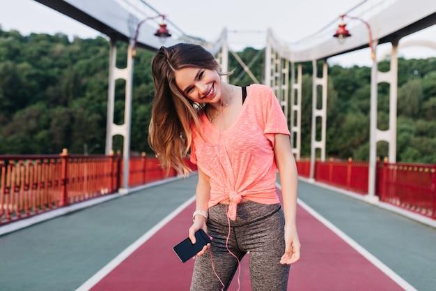 Modna dziewczyna stojąca z telefonem przy ścieżce żużlowej. roześmiana wspaniała kobieta słuchająca muzyki podczas treningu.