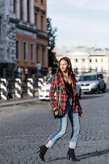 Modna dziewczyna w kraciastej kurtce i dżinsach spacerująca po mieście z czarną torebką.