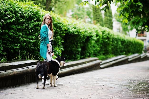 Modna dziewczyna w okularach i podartych dżinsach z rosyjsko-europejskim psem laika (husky) na smyczy, na ulicy miasta