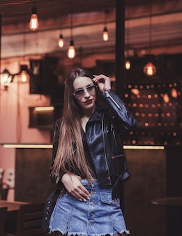 Modna dziewczyna w okularach przeciwsłonecznych i skórzanej kurtce
