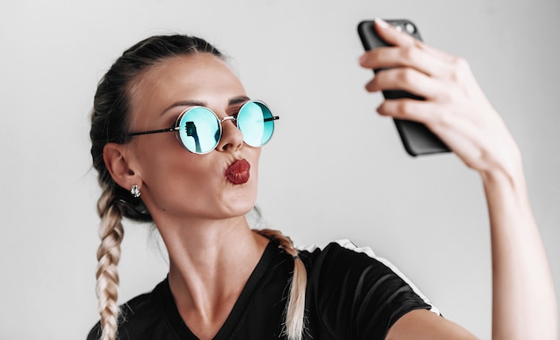 Modna dziewczyna w okularach przeciwsłonecznych w kolorowych okularach robi selfie na telefonie