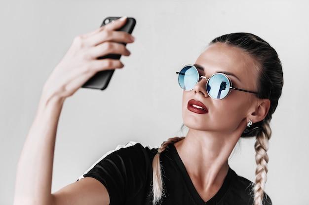 Modna dziewczyna w okularach przeciwsłonecznych w kolorowych okularach robi selfie przez telefon