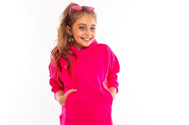 Modna dziewczyna w różowej bluzie, różowe okulary przeciwsłoneczne jest szczęśliwa i trzyma ręce w kieszeniach, na białym tle