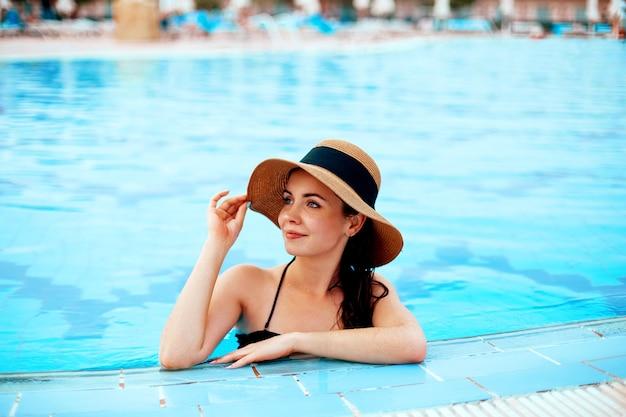 Modna dziewczyna w stylowym kapeluszu w basenie