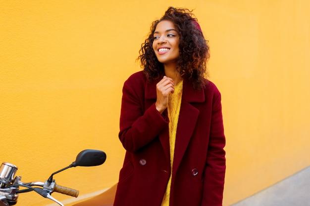 Modna dziewczyna w zimowym stroju i akcesoriach pozuje na żółto.