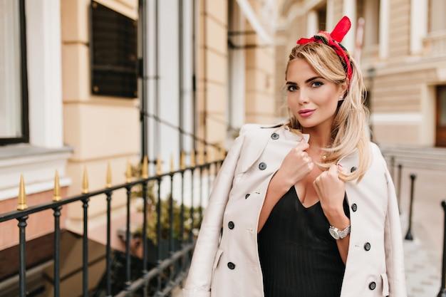Modna dziewczyna z kolorową wstążką w blond włosach figlarnie pozuje w zimny jesienny dzień stojąc w pobliżu sklepu. plenerowy portret uroczej jasnowłosej modelki owiniętej w beżowy płaszcz.