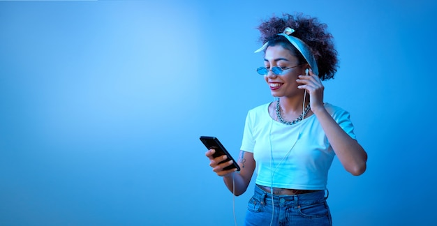 Modna dziewczyna z lokami w stylu afro słucha muzyki i słucha muzyki w słuchawkach w niebieskim świetle neonu