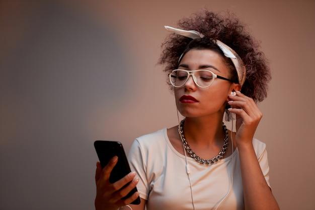 Modna dziewczyna z lokami w stylu afro używa smartfona i słuchawek na brązowej ścianie z miejscem na kopię
