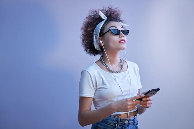 Modna dziewczyna z lokami w stylu afro używa smartfona i słuchawek na niebieskiej ścianie z miejscem na kopię