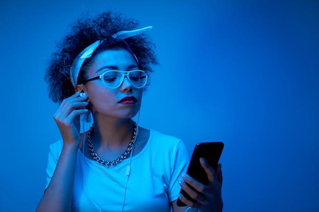 Modna dziewczyna z lokami w stylu afro używa smartfona i słuchawek z miejscem na kopię