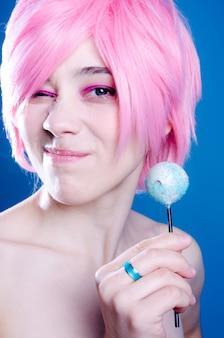 Modna dziewczyna z różowymi włosami trzyma niebieskie cukierki
