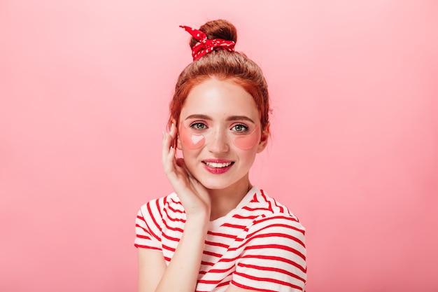 Modna dziewczynka kaukaski z opaskami na oku patrząc na kamery z uśmiechem. strzał studio imbir kobiety w paski t-shirt na białym tle na różowym tle.