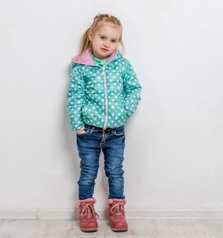 Modna dziewczynka w dżinsach, kurtce i butach