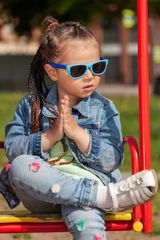 Modna dziewczynka z warkoczykami i okularami przeciwsłonecznymi siedzi na huśtawce splecionych w dłonie