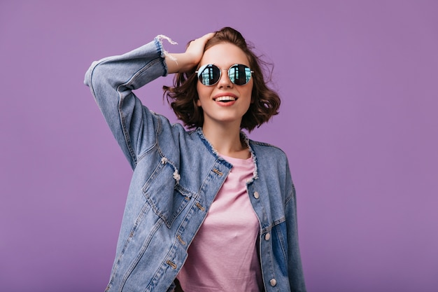 Modna emocjonalna kobieta w czarujący strój z uśmiechem dobrze ubrana biała dziewczyna w stojących okularach przeciwsłonecznych.