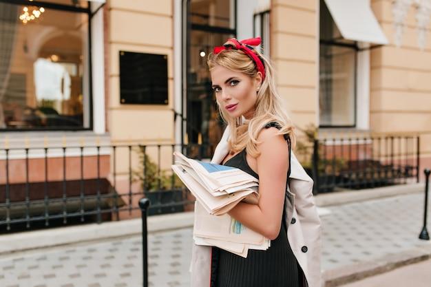 Modna europejska dziewczyna z czerwoną wstążką we włosach, patrząc z delikatnie uśmiechem