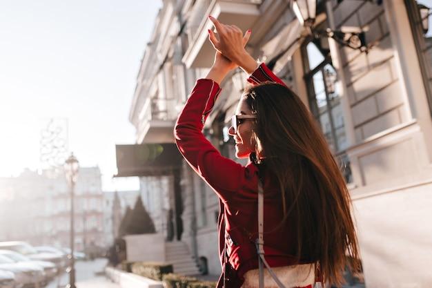 Modna europejska kobieta o długich ciemnych włosach zwiedza miasto w słoneczny dzień