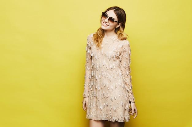 Modna i seksowna blondynka modelka z jasnym makijażem, w stylowej brzoskwiniowej sukience i modnych okularach przeciwsłonecznych, uśmiecha się i pozuje