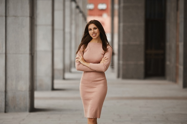 Modna i seksowna młoda kobieta o idealnym ciele, w beżowej stylowej sukience, stojąca z założonymi rękami i pozująca na ulicy