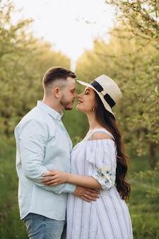 Modna i stylowa szczęśliwa kobieta w ciąży i jej mąż ubierali pastelowy biało-niebieski odcień w ogrodzie o zachodzie słońca