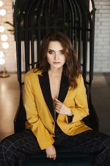 Modna i zmysłowa brunetka modelka z jasnym, idealnym makijażem, w stylowej złotej kurtce i modnych kraciastych spodniach siedzi na krześle i pozuje do wnętrza.