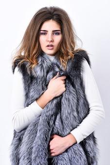 Modna kamizelka z futra srebrnego. luksusowe futro. dziewczyna makijaż twarzy długie fryzury nosić futro kamizelki białe tło. koncepcja trendu mody. butik sprzedający luksusowe futra. zimowa modna szafa.