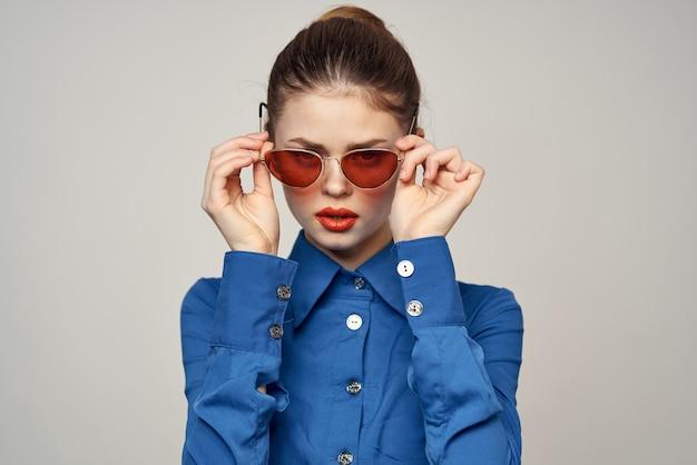 Modna kobieta gestykuluje rękami w okularach przeciwsłonecznych i błękitnej koszuli