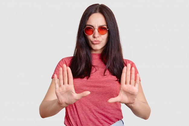 Modna kobieta jest z czegoś niezadowolona, pokazuje gest odmowy, trzyma dłonie z przodu, nosi okulary przeciwsłoneczne, różową koszulkę, na białym tle. przestańcie, proszę! nie przeszkadzaj mi