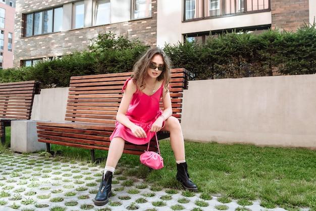 Modna kobieta modelka pozuje w różowej sukience i okularach, siedząc na ławce w pejzażu miejskim