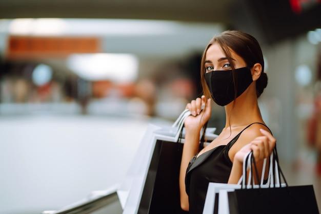 Modna kobieta nosi ochronną maskę medyczną z torby na zakupy w centrum handlowym.