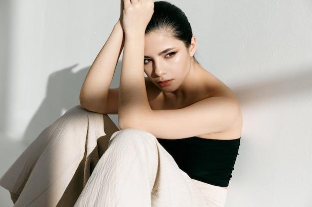 Modna kobieta pozuje siedząc na podłodze w pomieszczeniu i trzymając się za ręce blisko twarzy