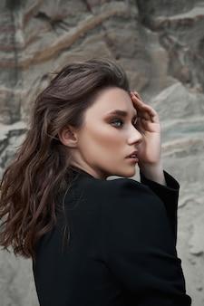 Modna kobieta pozuje w pobliżu piaszczystych skał
