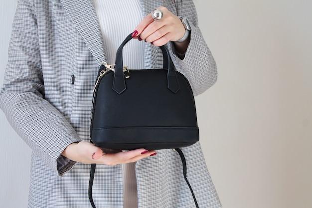 Modna kobieta trzyma czarną skórzaną torbę. miejsce na twój tekst