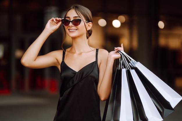 Modna kobieta ubrana w czarną sukienkę z torbami na zakupy.
