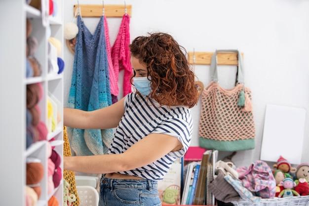 Modna kobieta ubrana w higieniczną maskę na twarz idzie na zakupy po ubrania