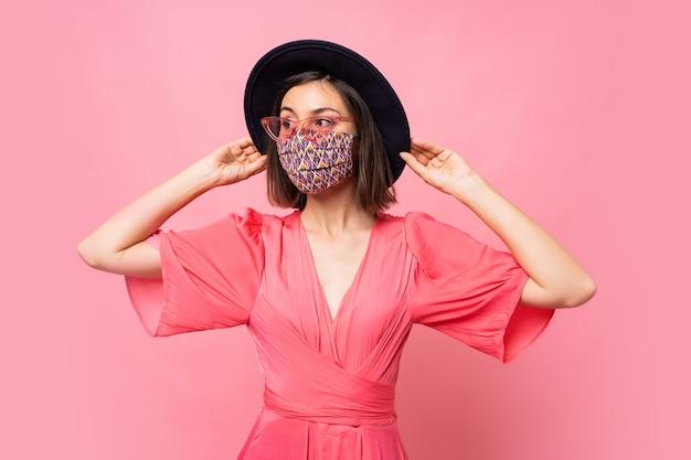 Modna kobieta ubrana w stylową maskę ochronną. nosi czarny kapelusz i okulary przeciwsłoneczne. pozowanie na różowej ścianie