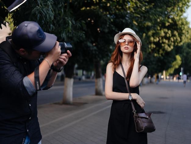 Modna kobieta w czarnej sukience i białym kapeluszu odpoczywa na łonie natury na ulicy w parku