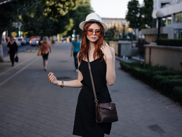 Modna kobieta w czarnej sukience i torbie na okulary na ramieniu parku przyrody