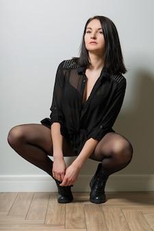 Modna kobieta w czarnych rajstopach na nogach i stylowych skórzanych butach