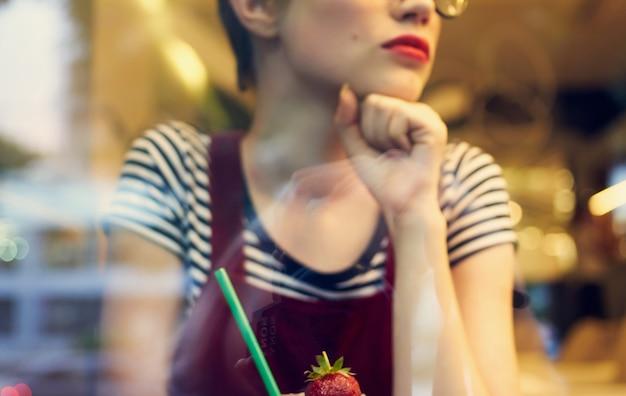 Modna kobieta w czerwonej sukience siedzi w kawiarni i lustrzane odbicie samochodów na ulicy