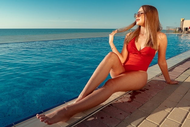 Modna kobieta w czerwonym bikini siedzi przy basenie