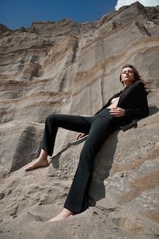 Modna kobieta w garniturze pozuje na piaskowych skałach