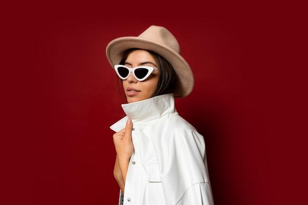 Modna kobieta w kapeluszu, sukience i białej kurtce, pozowanie. moda zimowa.