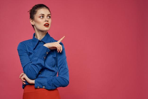 Modna kobieta w niebieskiej koszuli na różowym tle czerwona spódnica model emocji gestykuluje rękami przyciętymi widok copy space. wysokiej jakości zdjęcie