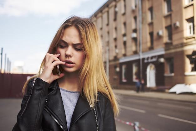 Modna kobieta w okularach przeciwsłonecznych na ulicy rozmawia przez telefon