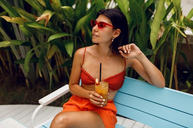 Modna kobieta w retro okularach przeciwsłonecznych relaksująca w klubie tropikalnej plaży w stylowym czerwonym topie i pomarańczowych szortach. picie smacznej lemoniady.