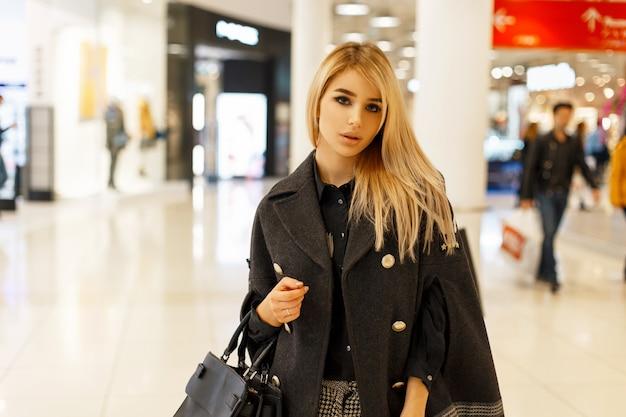 Modna kobieta w stylowym modnym płaszczu z torebką w centrum handlowym
