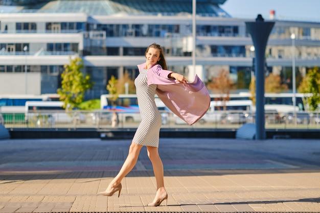 Modna kobieta w sukience w paski rzuca na zewnątrz otwarty liliowy płaszcz