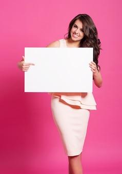 Modna kobieta, wskazując na pustą tablicę
