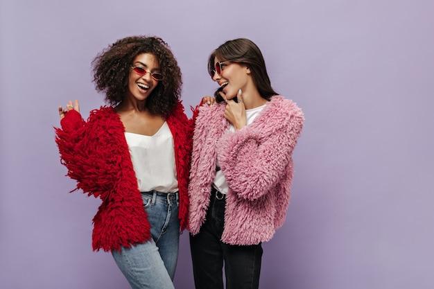 Modna kobieta z falującymi włosami w białym topie, dżinsach i czerwonym modnym swetrze uśmiecha się i pozuje z nowoczesnym przyjacielem w różowym ciepłym stroju